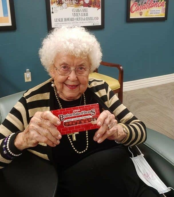 senior woman smiles in the movie theatre room with her candy