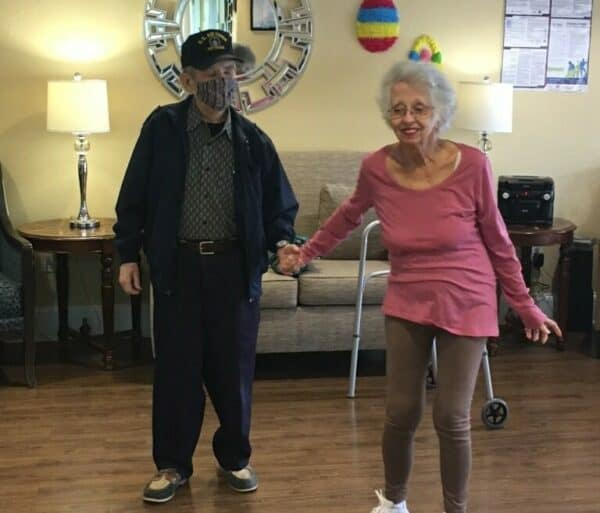 Senior man and woman dance together at a senior living facility in Richardson, Texas.