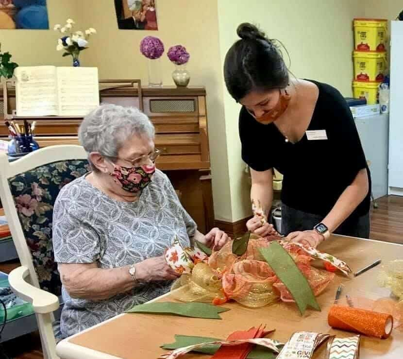 Senior woman and employee make flower craft at a senior living community in Fitchburg, Wisconsin.