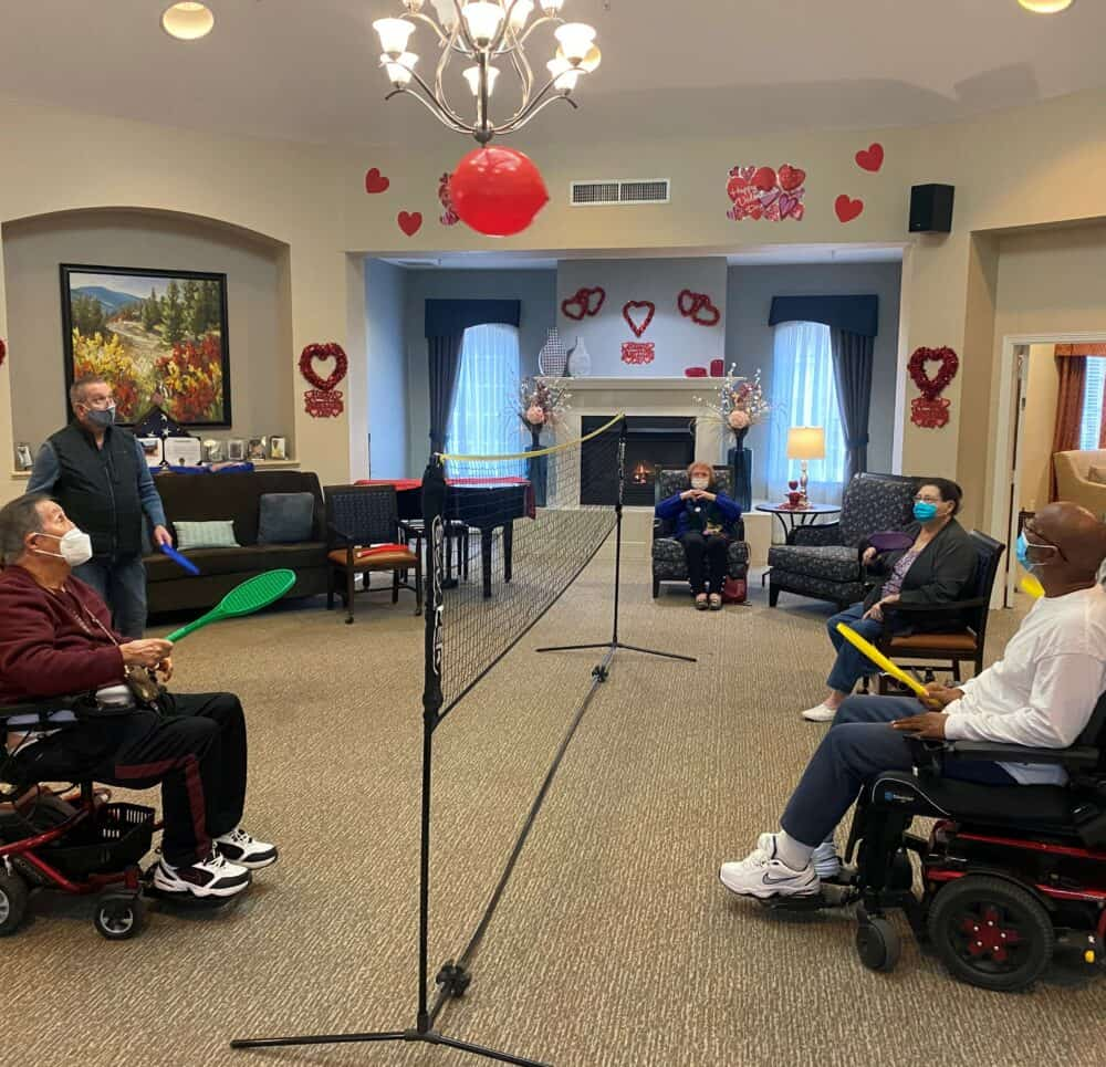 Group of seniors play a game of indoor volleyball at a senior living facility in Richardson, Texas.