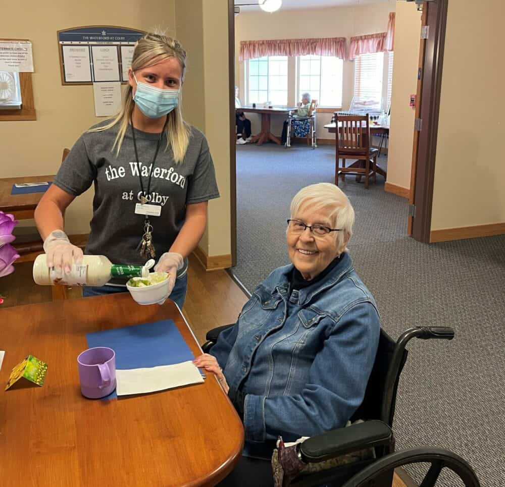 senior living worker helps a senior woman with her meal at the waterford at colby