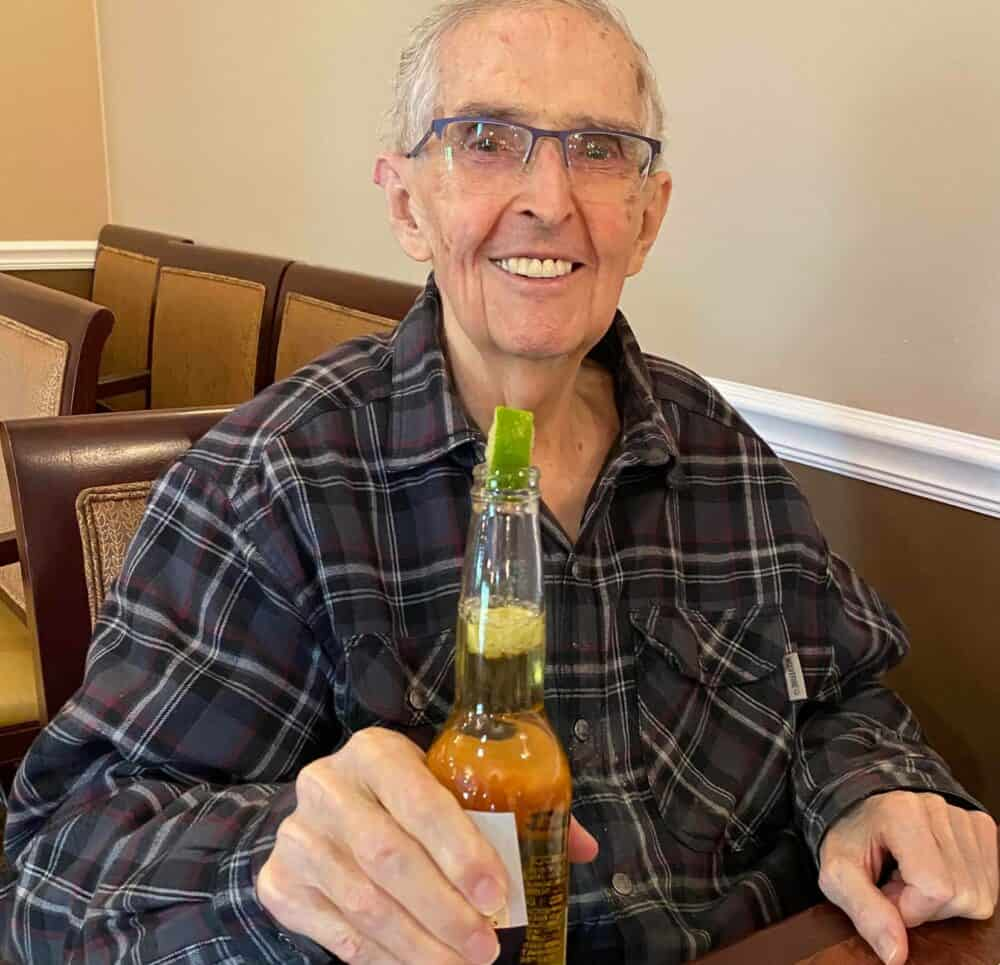 Senior man smiles with his beer at a senior living community in Fitchburg, Wisconsin.