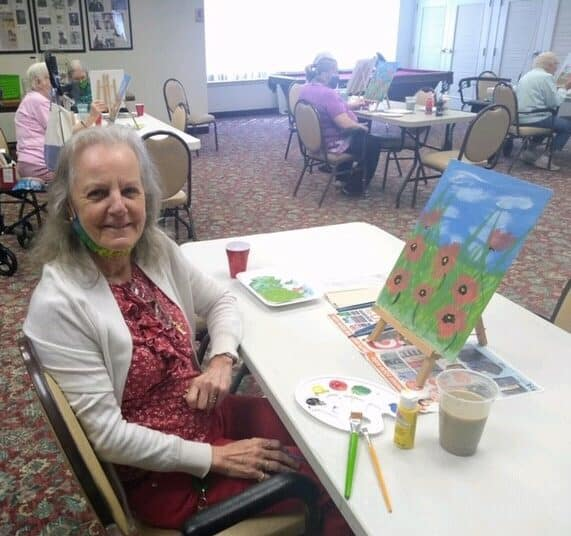 Senior woman smiles with her painting at a senior living facility in Fairfield, Ohio.