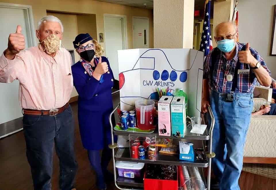 Two senior men pose with an airline woman at senior living community in Cottonwood, Arizona.
