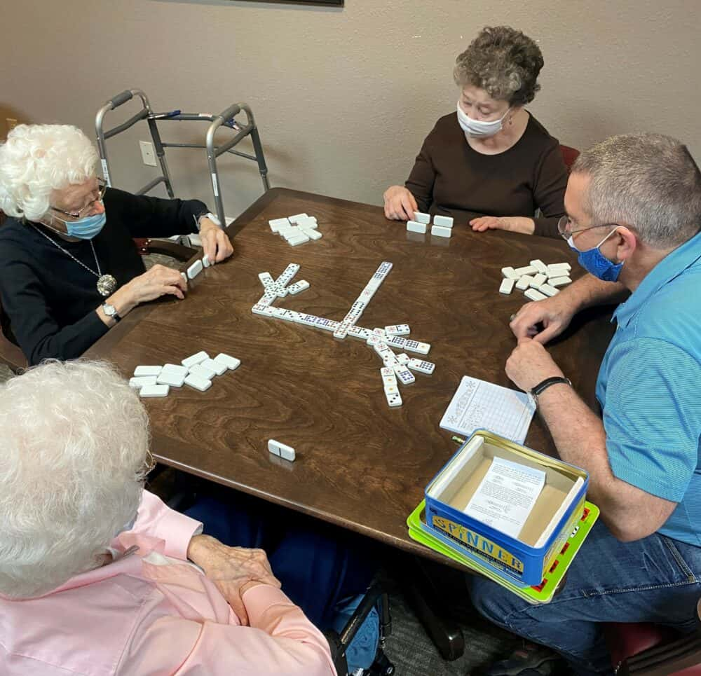 group of seniors playing a game at a table at the wellington at arapaho in Richardson, Texas