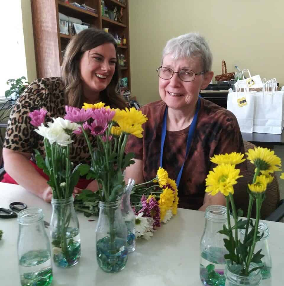 Two older ladies smiling with some yellow and pink flowers at Whitley Place in Keller, Texas.