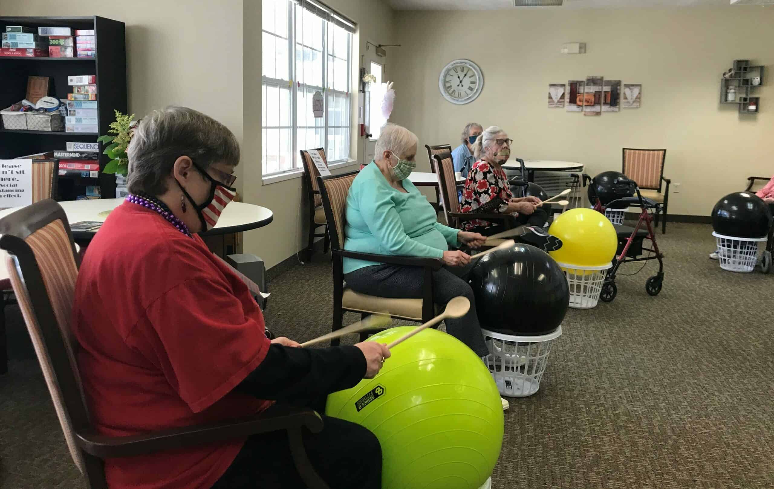 group of seniors doing a drum exercise at marquis place of elkhorn, a senior community in nebraska