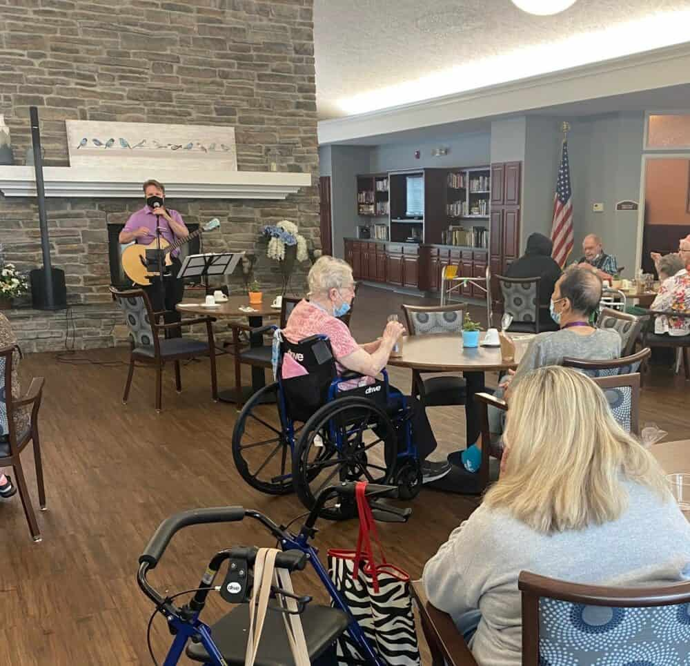 seniors enjoy listening to a performer at marquis place of elkhorn, a senior community in nebraska