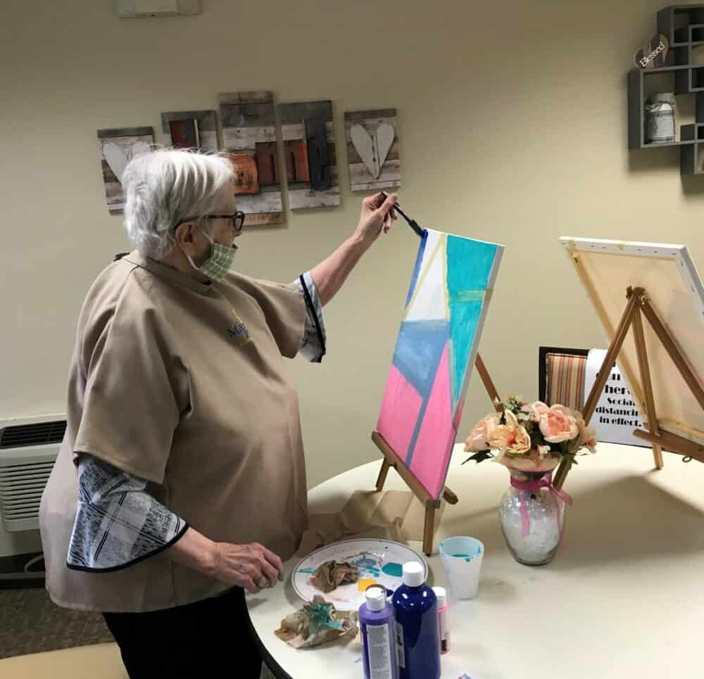 senior woman paints a canvas at marquis place of elkhorn, a senior community in nebraska