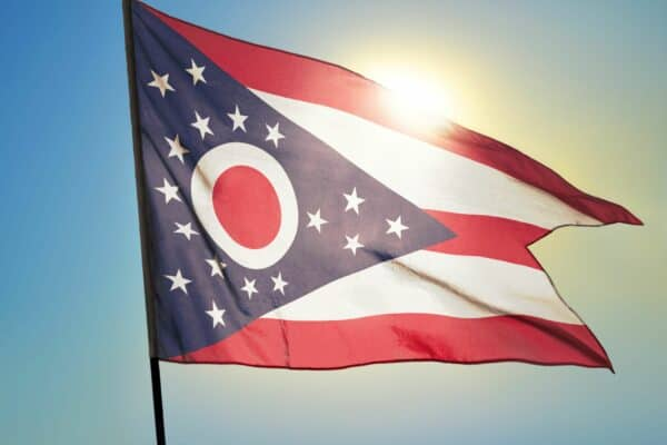 Ohio state of United States flag waving on the wind in front of sun.