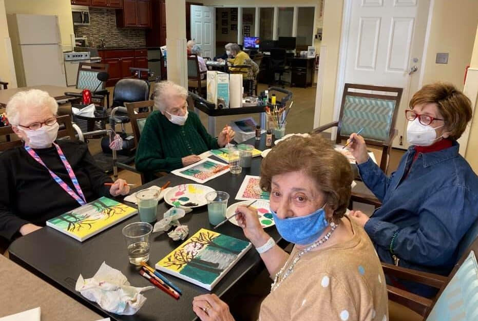 four older women painting together at a table