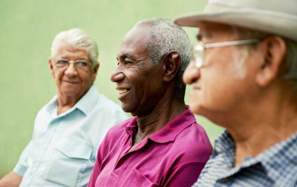 Three senior men sitting next to each other talking.