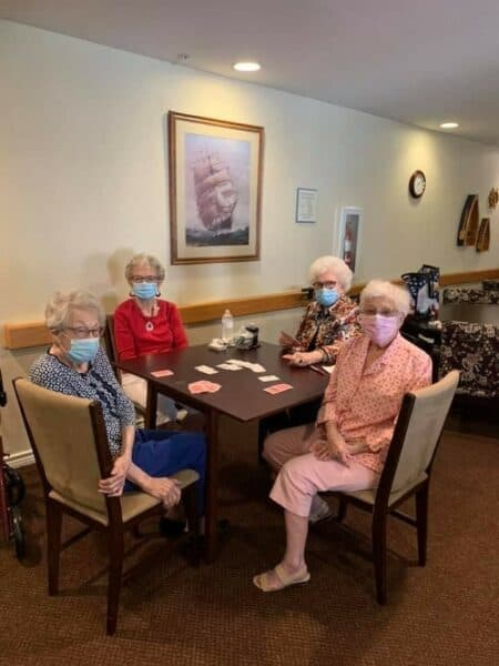 Four senior women with masks on play cards at a senior living community in Irving, Texas.