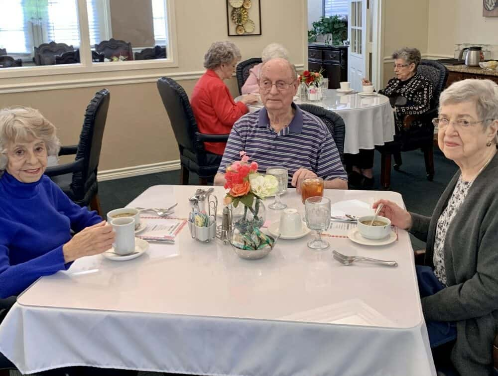 three seniors enjoy a drink together at the remington at valley ranch, a senior living community in Irving, Texas