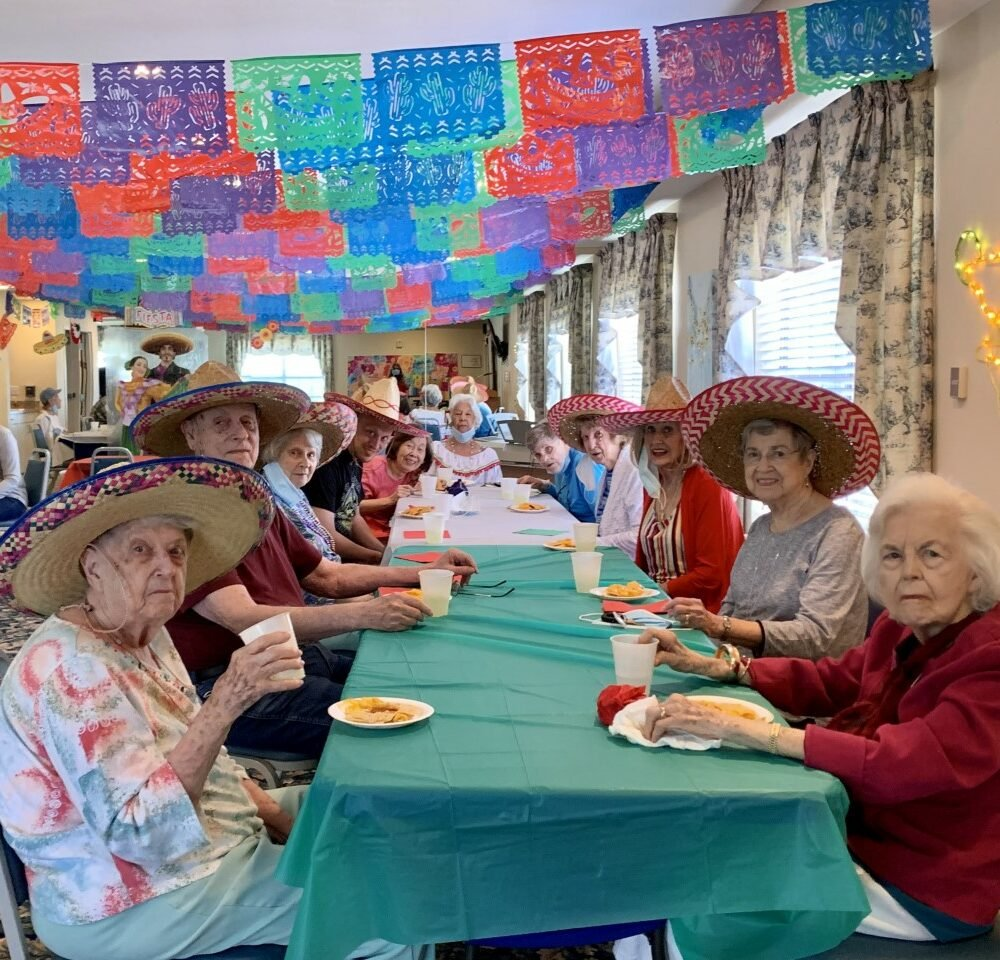 Group of seniors eat together during a Cinco de Mayo party at a senior living community in Irving, Texas.