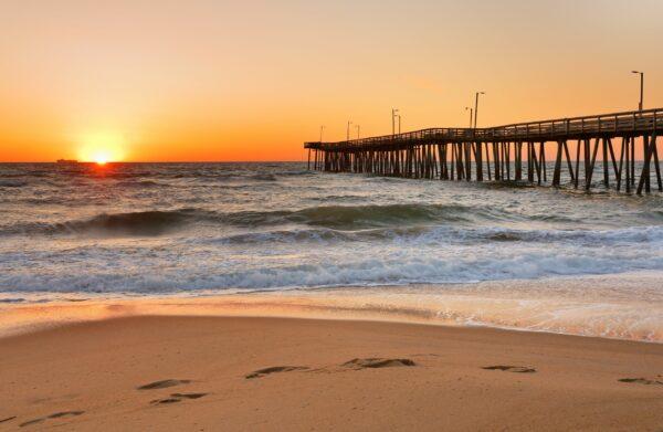 Fishing Pier at Sunrise at Virginia Beach, Virginia, USA. Virginia Beach, a coastal city in southeastern Virginia, lies where the Chesapeake Bay meets the Atlantic Ocean.