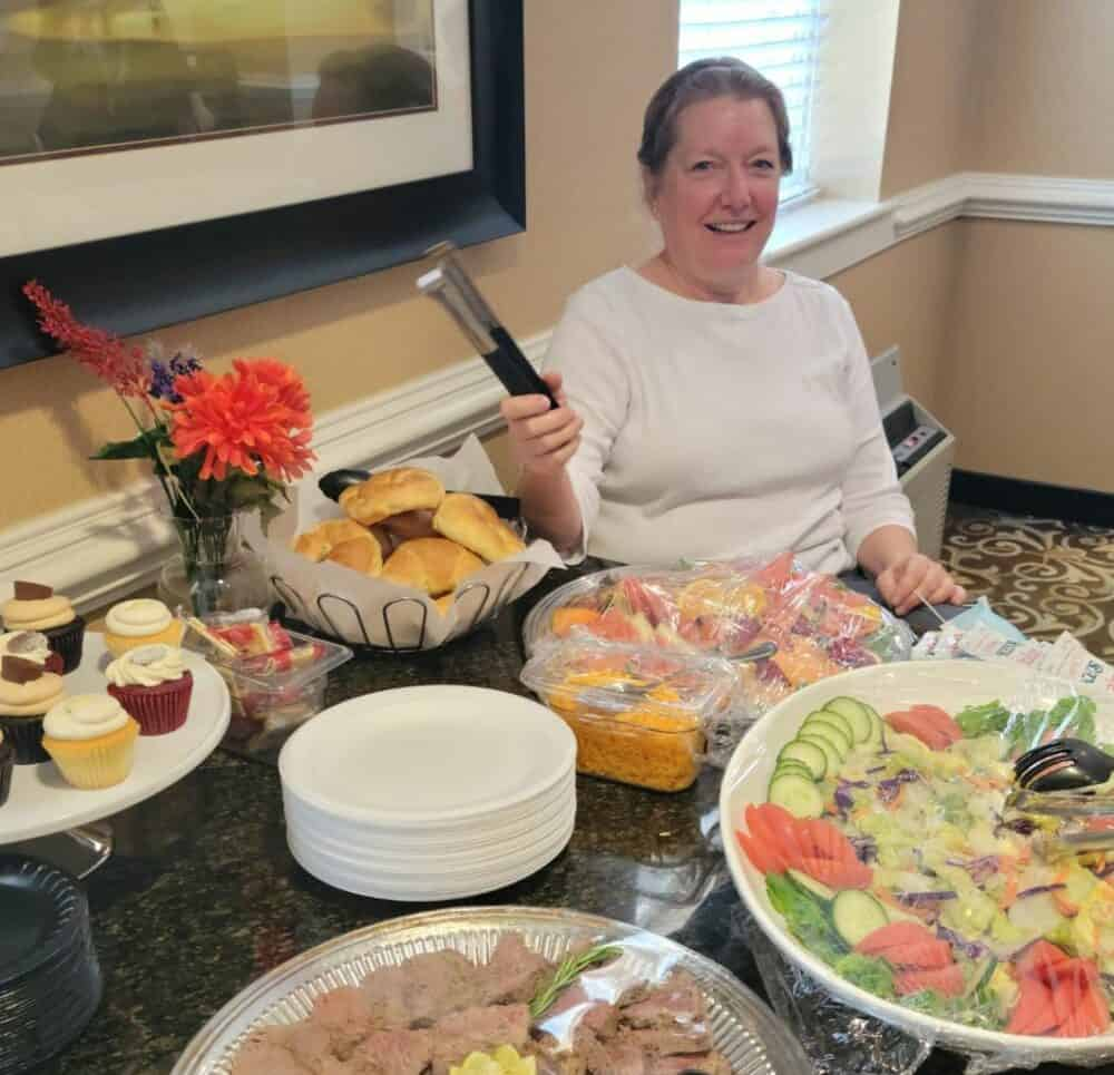 Senior woman surrounded by food for party at senior living facility in Virginia Beach, Virginia.