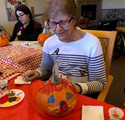 A smiling resident painting a pumpkin during a fall activity session.