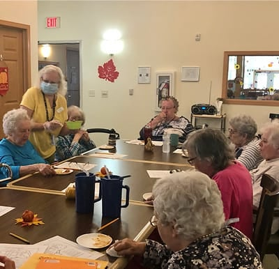 A group of senior women enjoying a treat together during a baking activity.