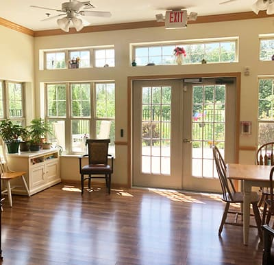 A bright sunroom with large windows and doors, seating and a piano.