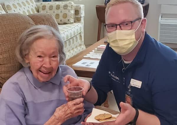 A caregiver wearing a mask and serving chocolate chip cookies and a beverage to a smiling resident.