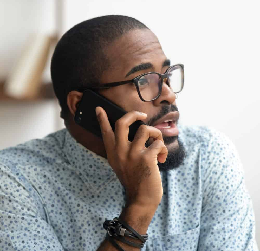Close up of man talking phone at workplace in office.