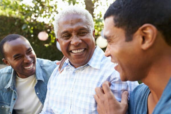 Senior man talking with his adult sons in garden.