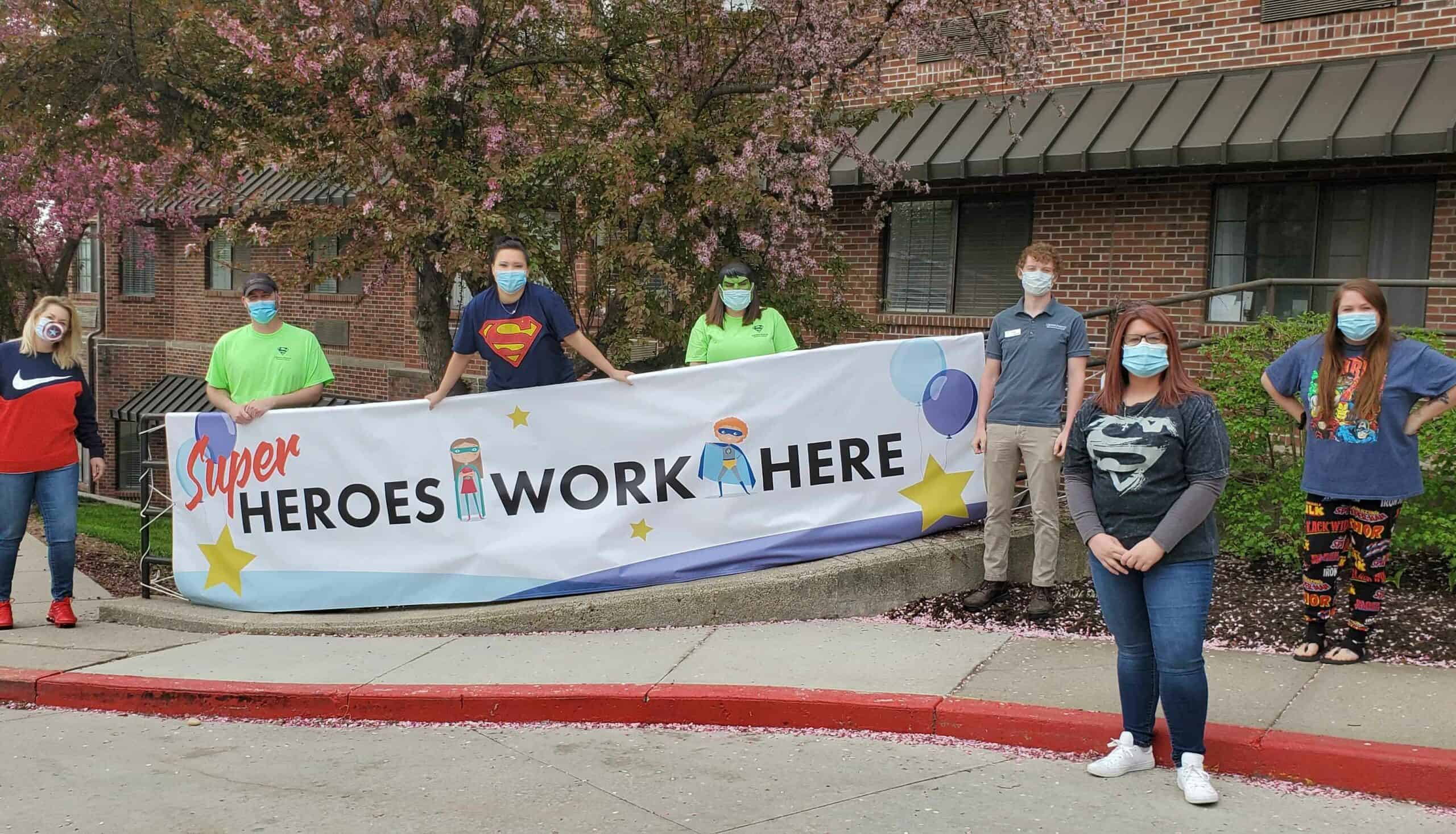 """A group of employees wearing masks, social distancing and holding up a sign that says """"HEROES WORK HERE""""."""
