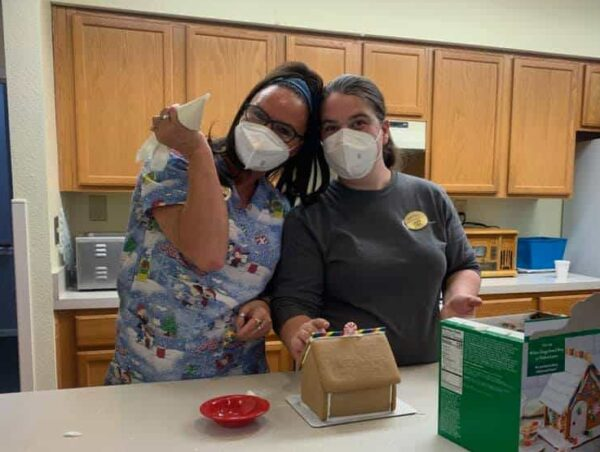 Two employees of senior living facility make a gingerbread house in Jeffersonville, Indiana.
