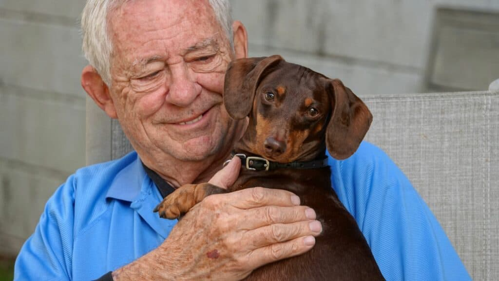 Close-up of a happy, smiling senior man holding his little dog