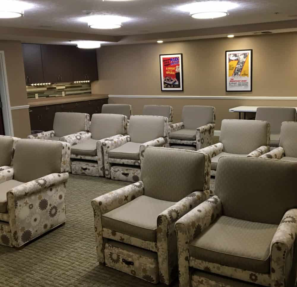 Rows of comfortable lounge seating in Canton Regency's on-site movie theatre. Complete with snack station and movie-style artwork hung on the walls.