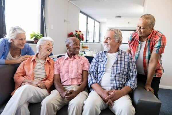 Smiling senior friends listening to man while sitting on sofa in nursing home.