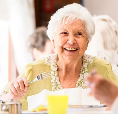 A smiling assisted living resident is enjoying a meal with friends in a well-lit dining hall.