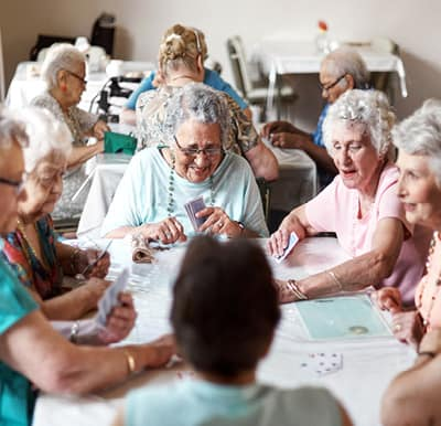 A group of senior women at a senior living community laughing over a game of cards in a well-lit activity room.