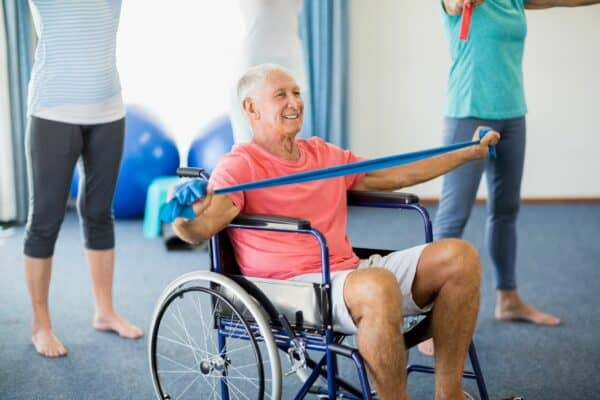 Senior in wheelchair exercising with exercising band during exercise class.