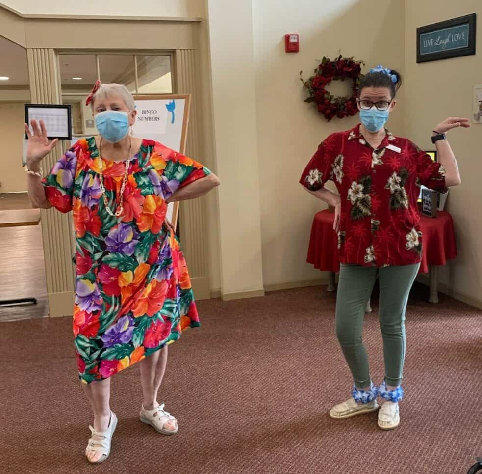 Senior living resident and employee dancing in Hawaiian outfits at a senior living community in Lincoln, Nebraska.